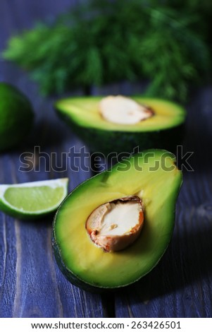 Sliced avocado with lime and herb on wooden table, closeup - stock photo