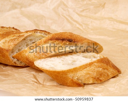 sliced baguette with brown paper - stock photo