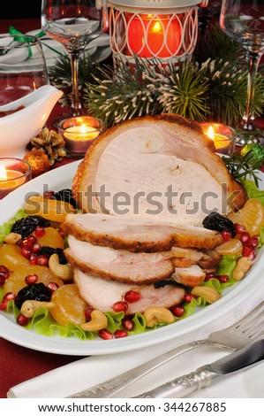 sliced baked turkey ham with fruit garnish on the Christmas table - stock photo