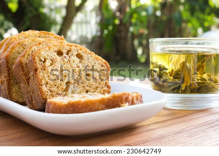 Sliced banana cake on white plate with a glass of tea and garden view background. Home made. - stock photo