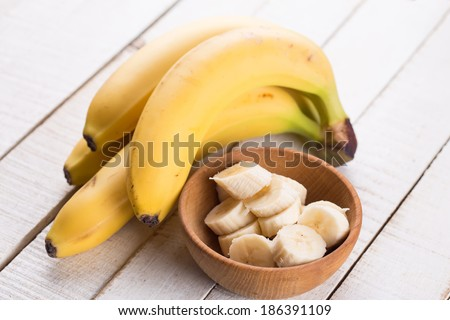 Sliced banana in bowl on white wooden background. Selective focus.