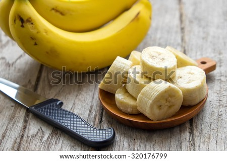 Sliced banana in glass on white wooden background. Selective focus. - stock photo
