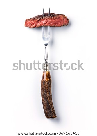 Sliced beef steak ribeye on meat fork on white background - stock photo