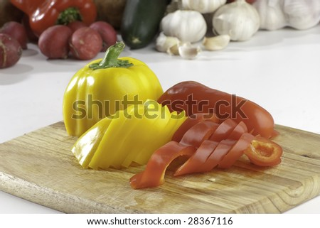Sliced bell peppers on wooden bread board on white background