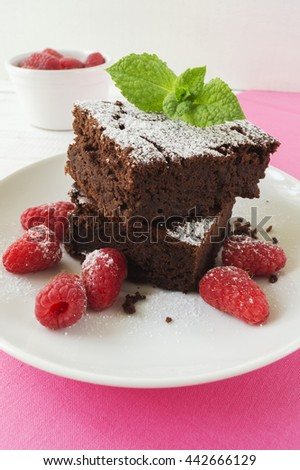 Sliced black bean brownie cake decorated with powdered sugar and mint and raspberry on white plate pink cloth napkin on white wooden table, selective focus, vertical, close up - stock photo