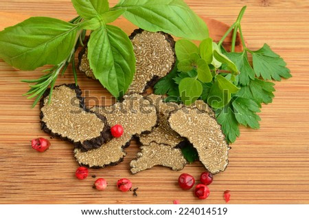 Sliced black truffle with fresh, green aromatic plants and red pepper on wooden background - stock photo