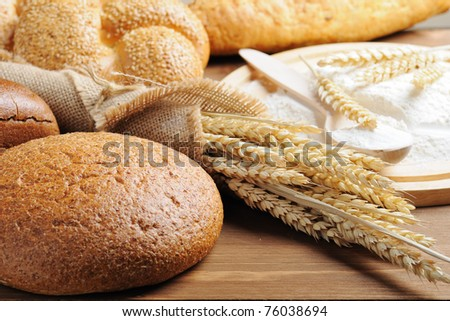 sliced bread and wheat on the wooden table - stock photo