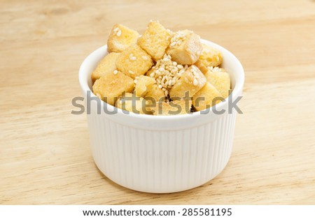 Sliced bread coated with caramel and sesame.In ceramic cup