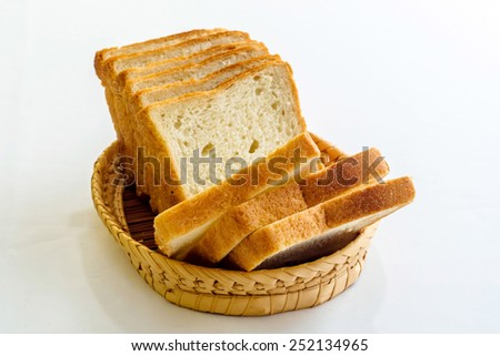 Sliced bread in wicker basket isolated on white - stock photo