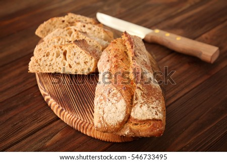 Sliced bread with knife on wooden background