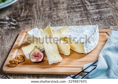 Sliced brie cheese on a wooden table and slices of figs - stock photo