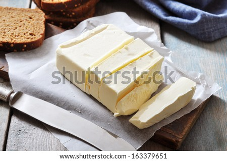 Sliced butter on wooden cutting board closeup