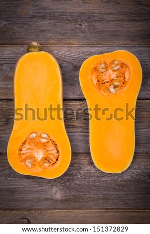 Sliced butternut squash over old wood background with intentional vignette - stock photo