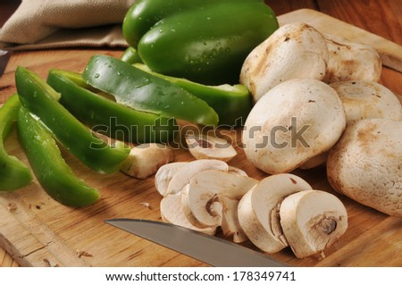 Sliced button mushrooms and green peppers on a cutting board