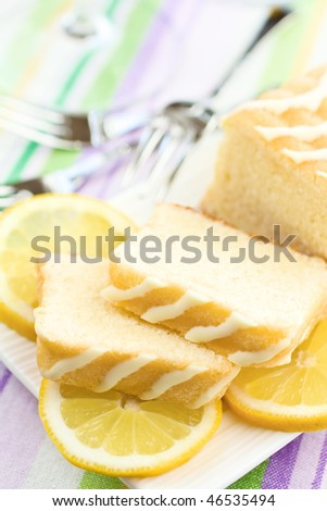 Sliced Cake On A Plate With Lemons - stock photo