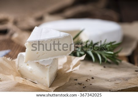 Sliced Camembert (close-up shot) on rustic wooden background - stock photo
