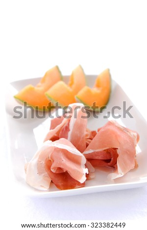 Sliced cantaloupe with piles of prosciutto, a type of Italian cured ham  - stock photo