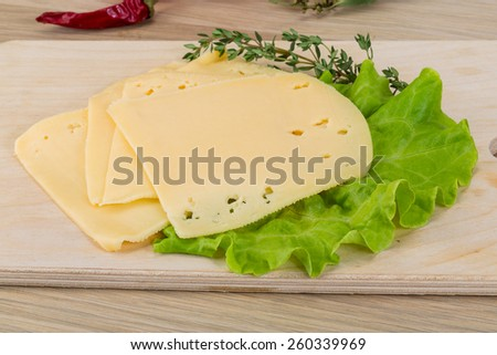 Sliced cheddar on the board with thyme - stock photo