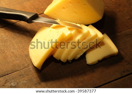 Sliced cheese and knife lying on wooden background - stock photo