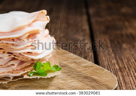 Sliced Chicken Breast fillet (selective focus) on wooden background - stock photo
