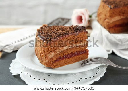 Sliced chocolate cake on plate, on wooden table  background