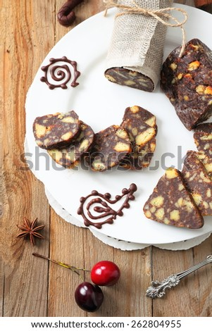 sliced chocolate sausage with various decorations on a wooden table