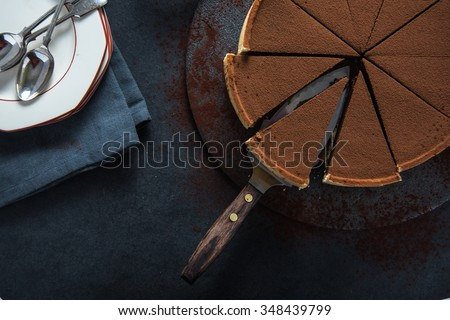Sliced chocolate tort on dark background, overhead view - stock photo