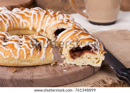 Sliced cinnamon pecan danish on a wooden patter
