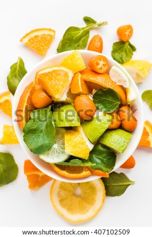 Sliced citrus fruit on the plate. Citrus salad on white background. Top view, flat lay   - stock photo