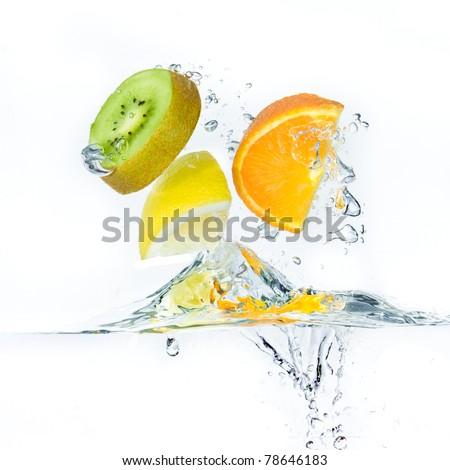 sliced citrus fruit with kiwi splashing isolated on white background - stock photo