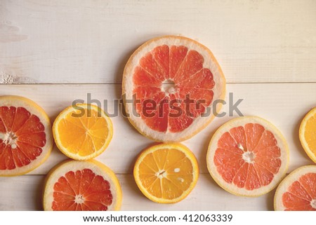 Sliced citrus fruits background  with a vintage tint. Oranges and grapefruits. Over white rustic table background with copy space. Top view