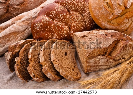 Sliced country-styled brown bread baton and rye spikes on the canvas tablecloth with bread loafs assortment - stock photo