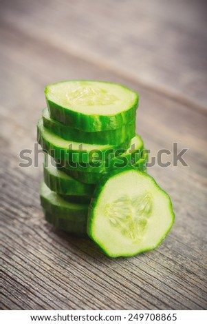 Sliced Cucumber in Stack on wood background - stock photo