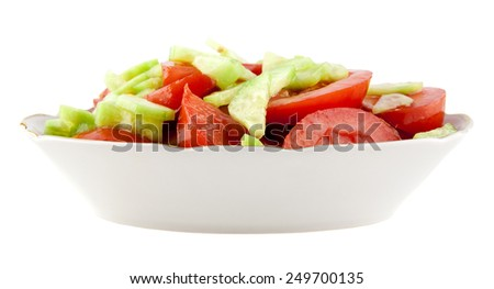 sliced cucumbers and tomatoes in a bowl on white background - stock photo