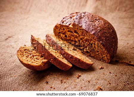 Sliced dark bread with crumbs on  sacking background - stock photo