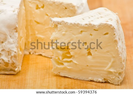 Sliced delicious brie cheese on wooden cutting board - stock photo