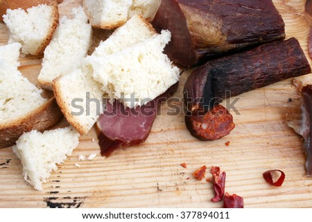 Sliced dried meat at old wooden table