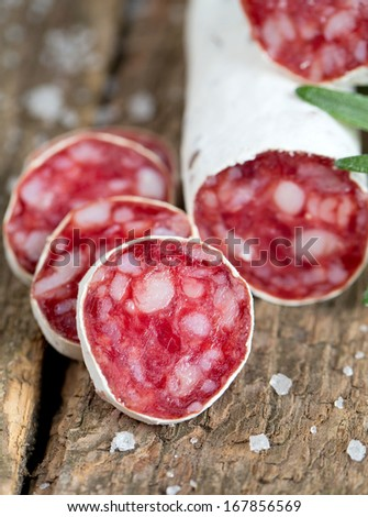 sliced dried salami on rustic wooden table - stock photo