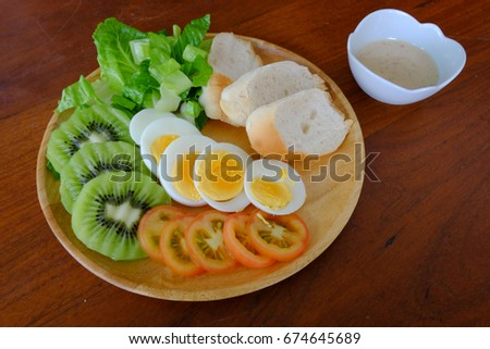 Sliced egg salad serve with vegetable, kiwi, tomato, crispy bread and separated sesame dressing (Forty five degree angle view )