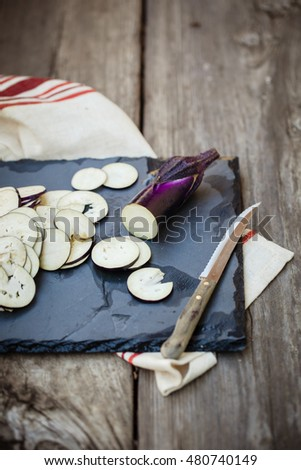 Sliced eggplants on a black board with wooden background. Also available in horizontal format.