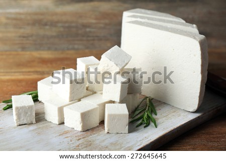 Sliced feta cheese with rosemary on table on wooden background - stock photo