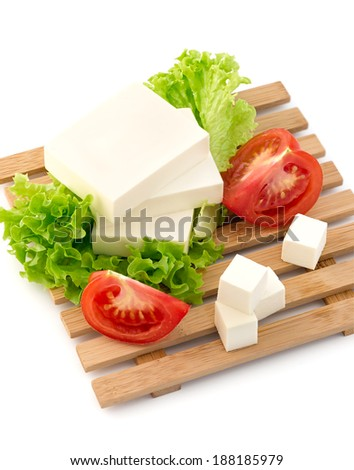 Sliced feta cheese with salad and tomato - stock photo