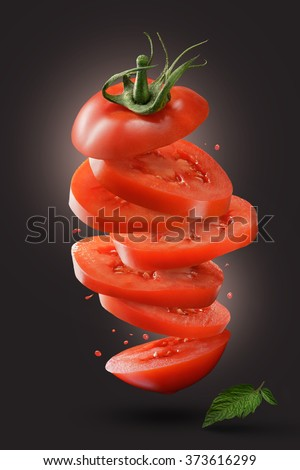 sliced flying tomato with green leaf on dark background - stock photo