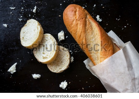 Sliced french baguette with crumbs on black background. Traditional fresh bread for breakfast - stock photo