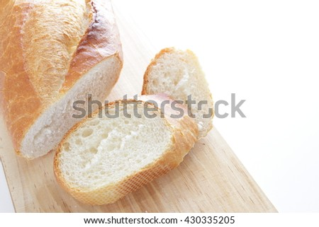 Sliced French bread on wooden board - stock photo