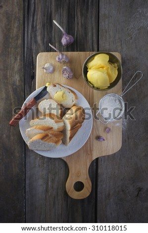 Sliced french loaf with garlic and butter on rustic kitchen counter top. Garlic bread preparation. Over head view. - stock photo