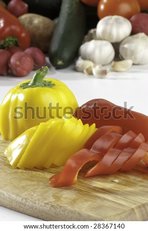 Sliced fresh bell peppers on background with a lot of vegetables