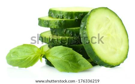 Sliced fresh cucumber with basil, isolated on white - stock photo