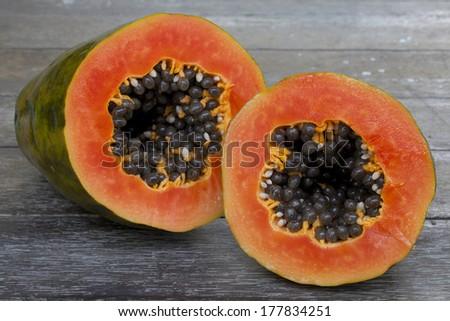 Sliced fresh papaya on wooden background - stock photo