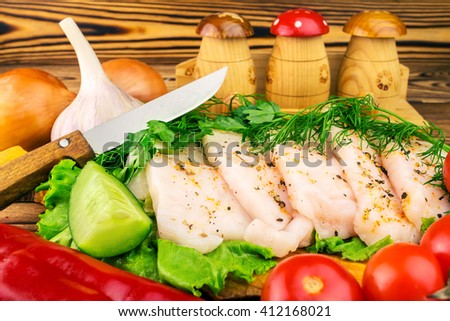 Sliced fresh pork lard, fresh produce, greens, vegetables on the wooden board and knife on table, selective focus - stock photo